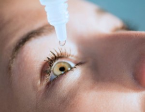 Squeezing eyedrops into the eye